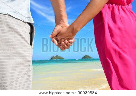 Beach couple in love holding hands on honeymoon. Pink dress, casual beachwear romantic newlyweds people standing on travel summer vacations on Lanikai beach, Oahu, Hawaii, USA with Na Mokulua Islands.