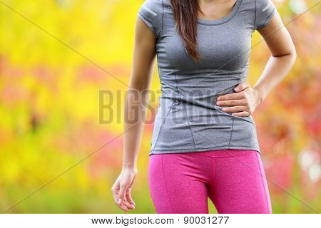Side cramps - woman runner side stitch after running. Jogging woman with stomach side pain after jogging work out. Female athlete in colorful late summer autumn forest.