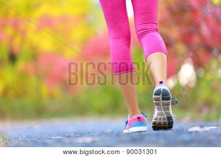 Jogging and running woman with athletic legs on jog or run on trail in forest in healthy lifestyle concept with close up on running shoes. Female athlete jogging and training outdoors in autumn fall.