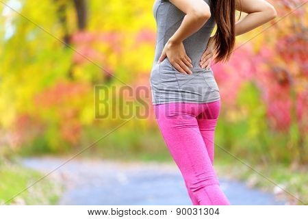 Back pain. Running woman with back injury in sportswear rubbing touching lower back muscles standing on road outside in forest in fall.