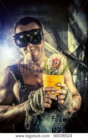 Strong muscular man coal miner holding a flower in a pot over dark grunge background. Mining industry. Greenpeace, environment protection.