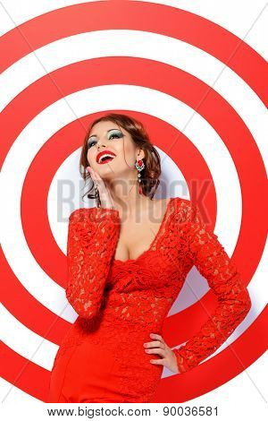 Magnificent young woman in bright red suit posing on a red target. Beauty, fashion. Isolated over white.