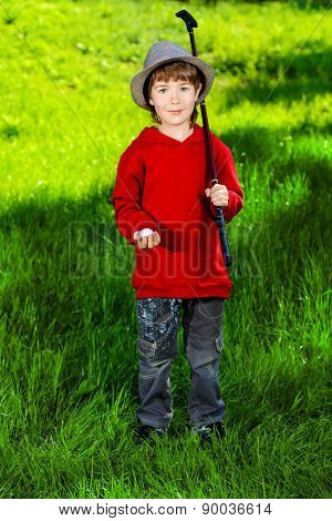 Cute 7 years old boy playing golf outdoor. Summer day.