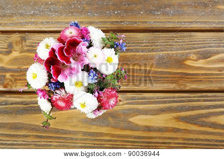 Colorful daisy on wooden table, top view