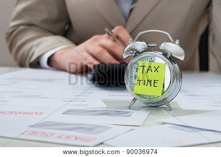 Businessman With Tax Time Reminder Note On Alarm Clock
