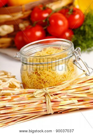 Italian Pasta with vegetables in wooden plate isolated on white.