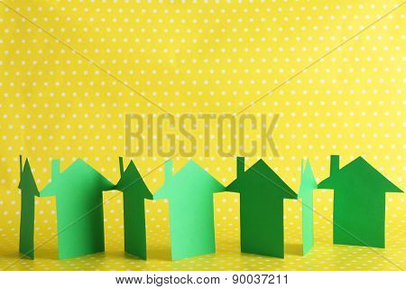 Paper houses on yellow dots background
