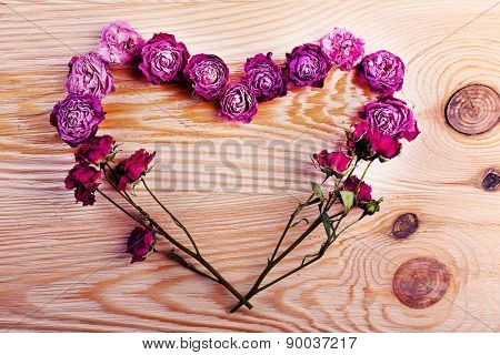 Heart from dried flowers on wooden background