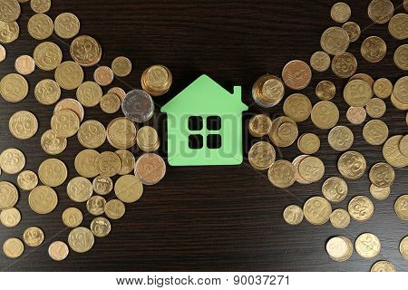 Model of house with coins on wooden table, closeup