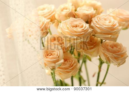 Bouquet of beautiful fresh roses on curtains background