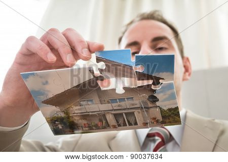 Businessman Making The House Of Puzzle