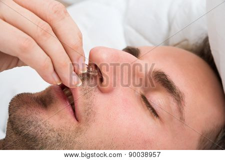 Person Hand Inserting Nose Clip Device Into Nose