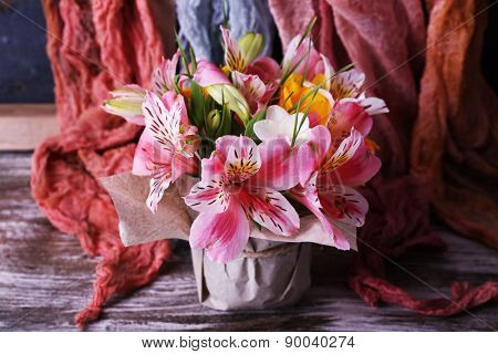 Beautiful flowers in vase on fabric background