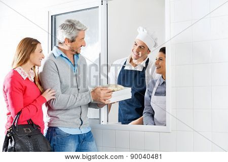Happy couple purchasing uncooked pasta packets from chefs through window