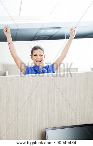 Portrait of successful female customer service representative with arms raised in cubicle