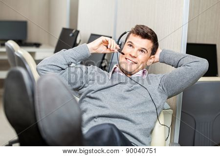 Smiling customer service representative adjusting headset with legs on desk in office