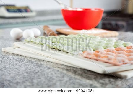 Raw ravioli pasta arranged on cutting board at countertop in commercial kitchen