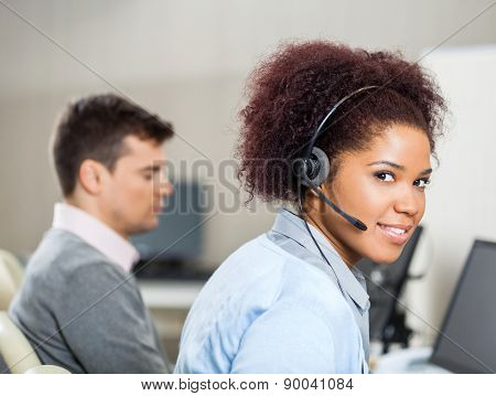 Portrait of female customer service representative wearing headset while colleague sitting in background at office desk