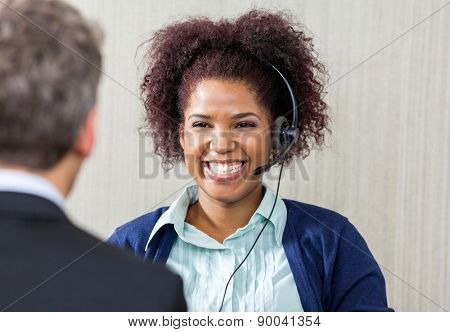 Happy female customer service executive wearing headset while looking at manager in office