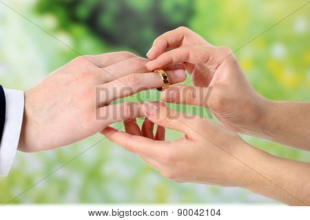 Woman and man holding wedding rings, close-up, on bright background
