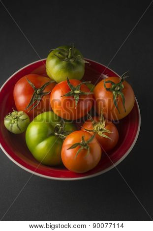Ripped and un-ripped tomatoes in a bowl on black background.