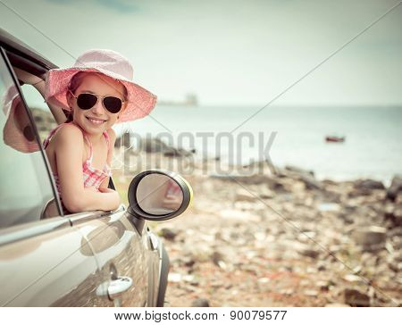 little girl traveling by car at sea