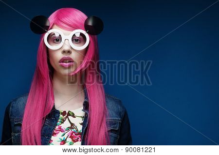 Beautiful fashion model  with pink hair and make-up wearing big sunglasses