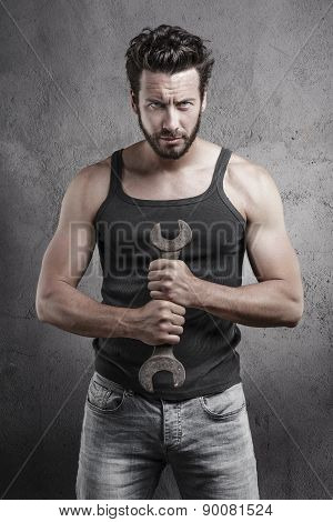 Handsome Rough Man Holding A Wrench Over A Textured Background