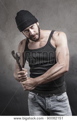 Thug preparing to use a wrench as a weapon with a dangerous angry expression over a textured grey background looking at camera poster