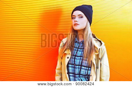 Fashion Portrait Of Stylish Pretty Woman Outdoors Against The Colorful Orange Wall