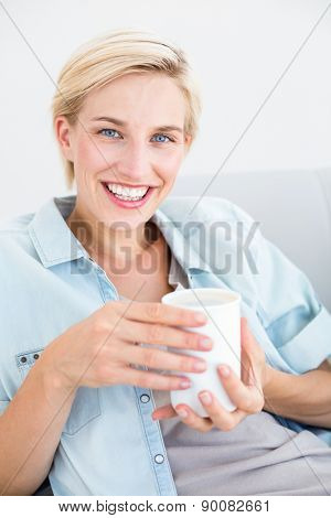 Pretty blonde woman relaxing on the couch and holding a mug in the living room