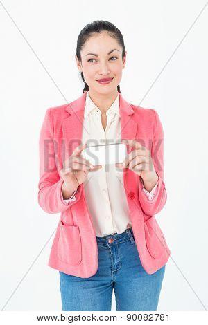 Elegant brunette holding her mobile phone on white background