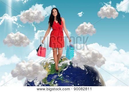 Woman standing with shopping bags against white cloud computing clouds