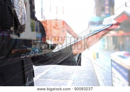 Businessman using his tablet pc against blurry new york street