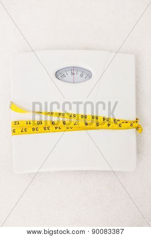 Weighing scales with measuring tape around on white background