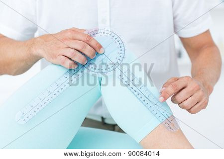 Doctor measuring knee with goniometer in medical office