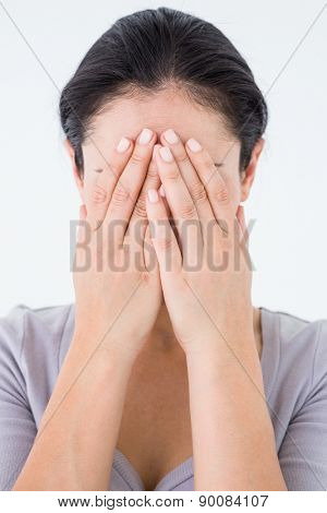 Sad woman hiding her face on white background