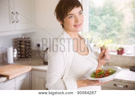Pregnant woman having bowl of salad at home in the kitchen