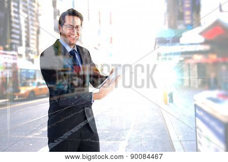Businessman looking at the camera while using his tablet against blurry new york street