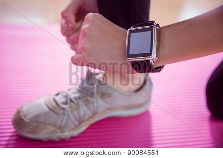 Woman trying her shoe lace at home in the living room