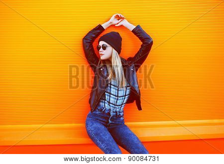 Street Fashion Concept - Stylish Cool Girl In Rock Black Style Posing Against A Colorful Orange Urba
