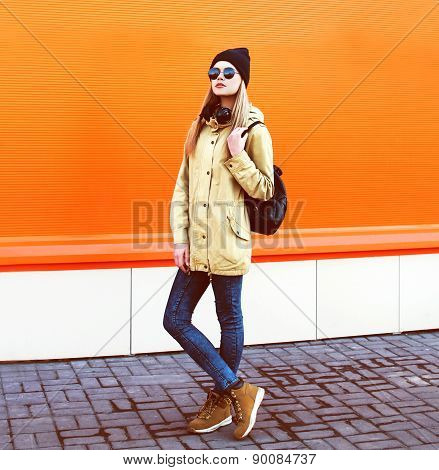 Street Fashion Concept - Stylish Hipster Girl In The City Against A Colorful Orange Urban Wall