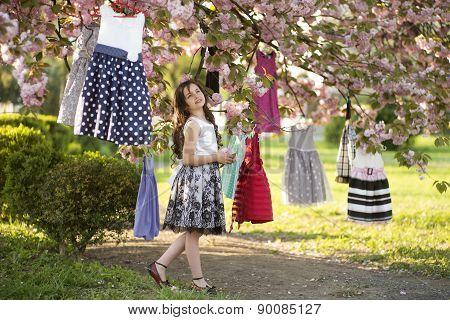Small Girl Among Dresses In The Tree