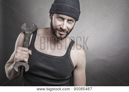 Handsome Rough Man Holding A Wrench Over A Textured Grey Background