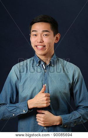 Smiling young Asian man giving the thumbs up sign and looking at camera