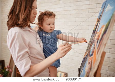 Young mother teaching her cute little daughter how to paint