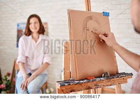 Hand of male artist drawing young woman on paper