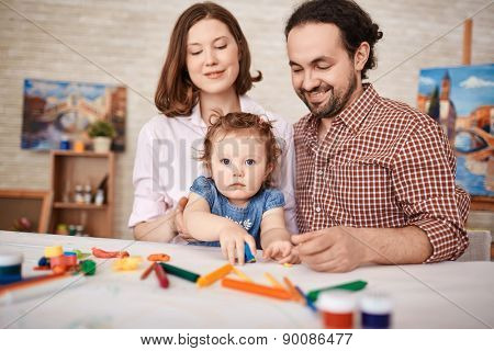 Young parents and pretty daughter playing together