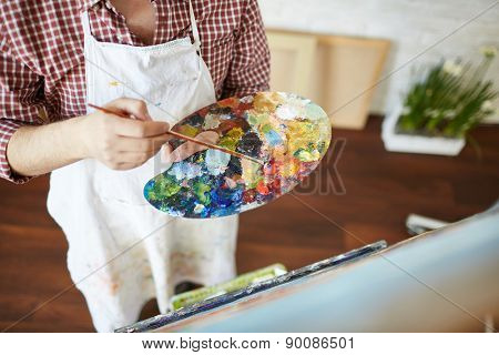 Close-up of artist hands with paintbrush and palette mixing water-colors