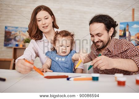 Young parents and their small daughter drawing together
